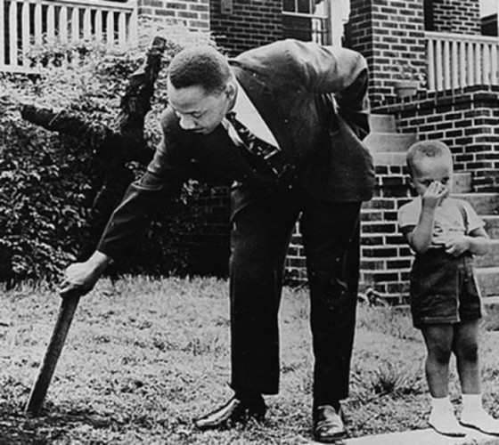 Martin Luther King removing a burnt cross from his front lawn as his 5-year-old son looks on.