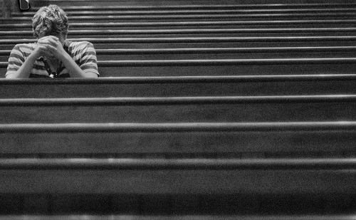 young-man-praying-in-one-of-several-rows-of-pews
