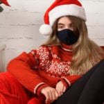 Woman dressed for Christmas wearing face mask looking sad