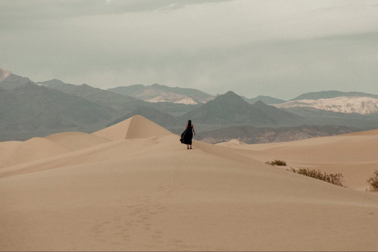 Quina Aragon walking away on a sand dune.