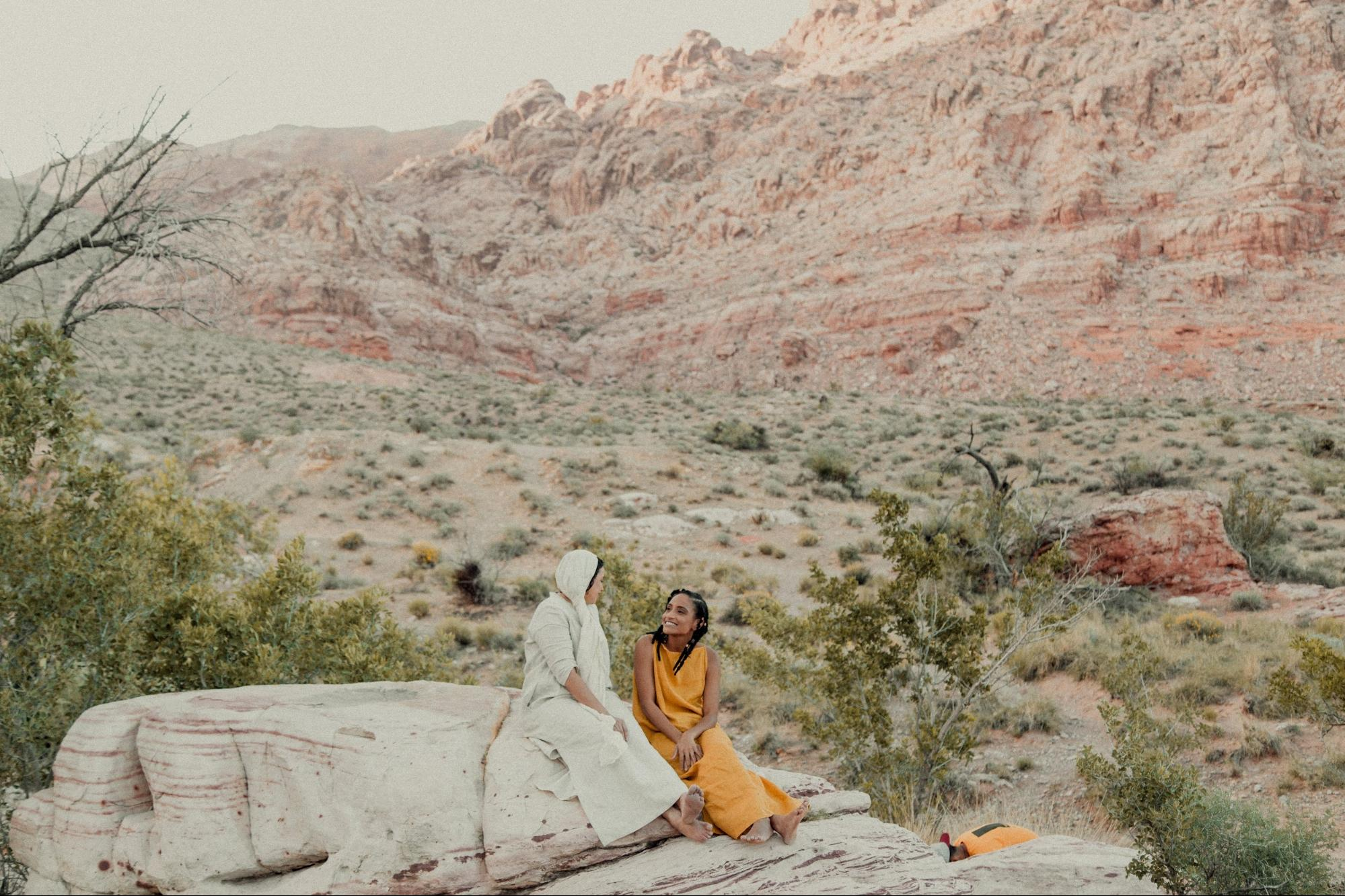 Quina Aragon and Karen Ellis sitting on a rock in the desert.
