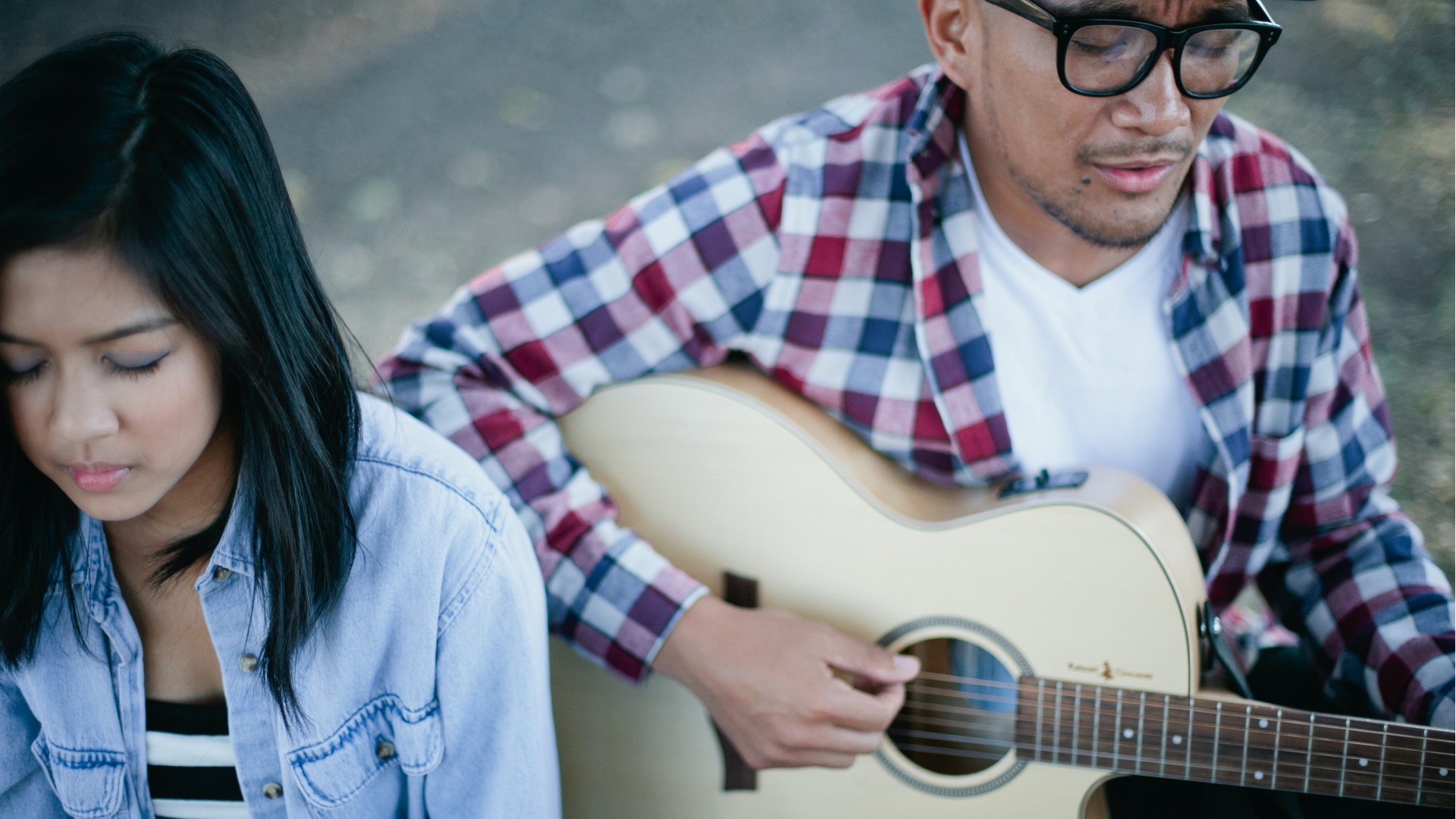 Man and woman singing together with guitar