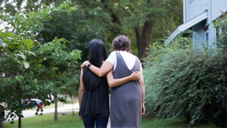 Two women talking while walking down sidewalk