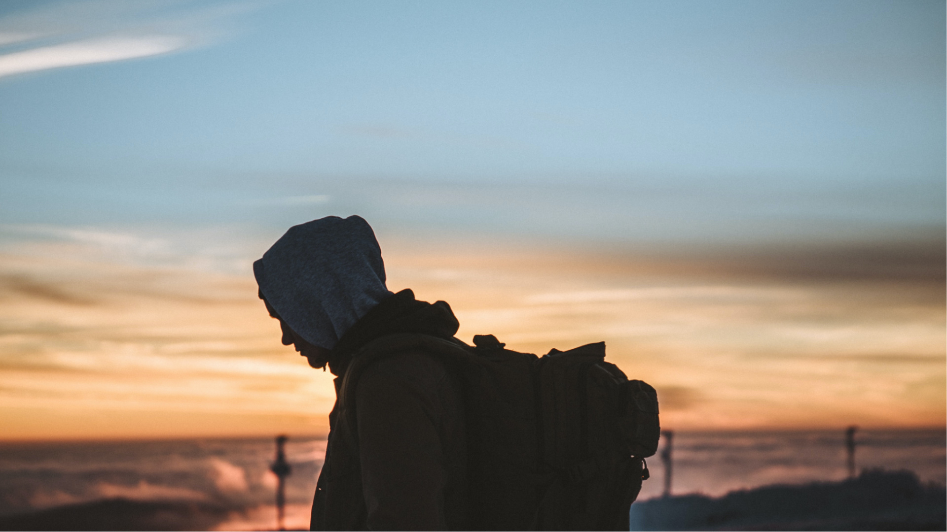 Silhouette of a man with backpack during sunset