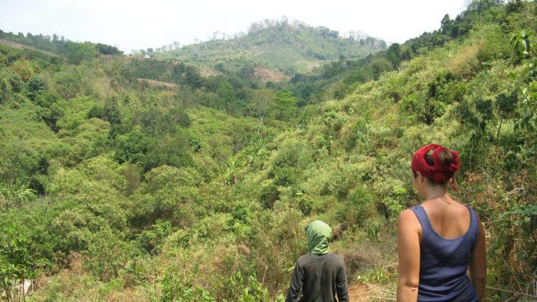 Two women walking on hillside trail in Ratanakiri, Cambodia