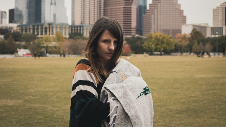 Homeless woman hold a blanket in the city