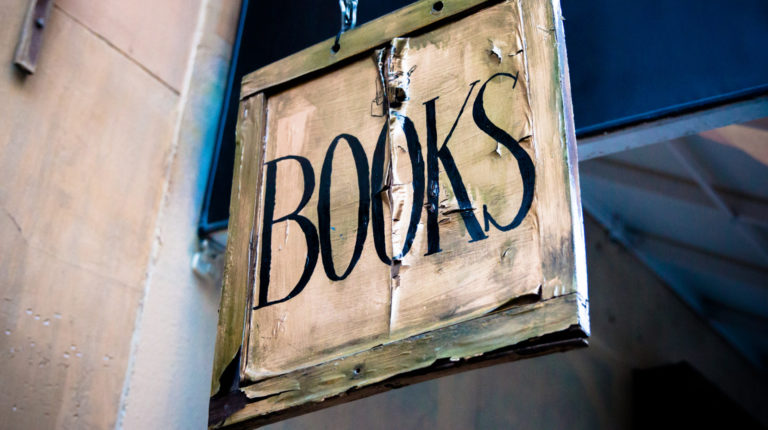 Aged book sign hanging above storefront