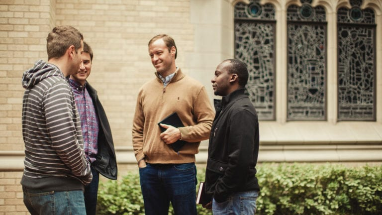Group of four men talking outside a church building