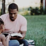 Dad, mom, and children reading Bible outside in a park