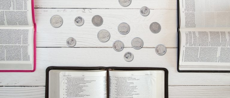 Economic transformation is hindered by bad theology. Open bibles on a table with scattered coins.