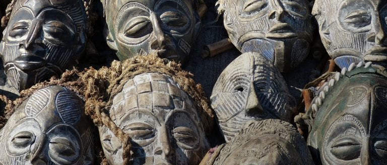 Witchcraft in Africa - image of carved wooden masks all together and on-top of each other