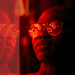 Woman wearing reflective sunglasses looking at red lights with the word reflected on her sunglasses. The purpose of this image is to show that when you look you can find.