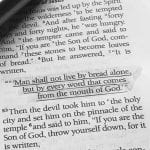 """Photo of The Bible with text underlined """"Man shall not live by bread alone"""""""