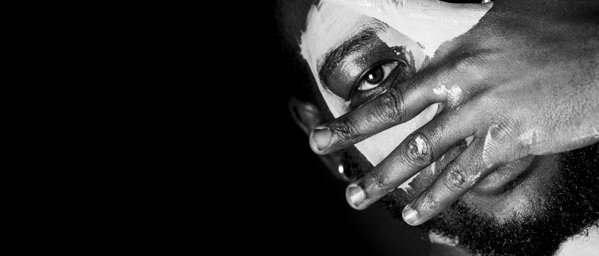 Manhood - man's face covered by hand on black background