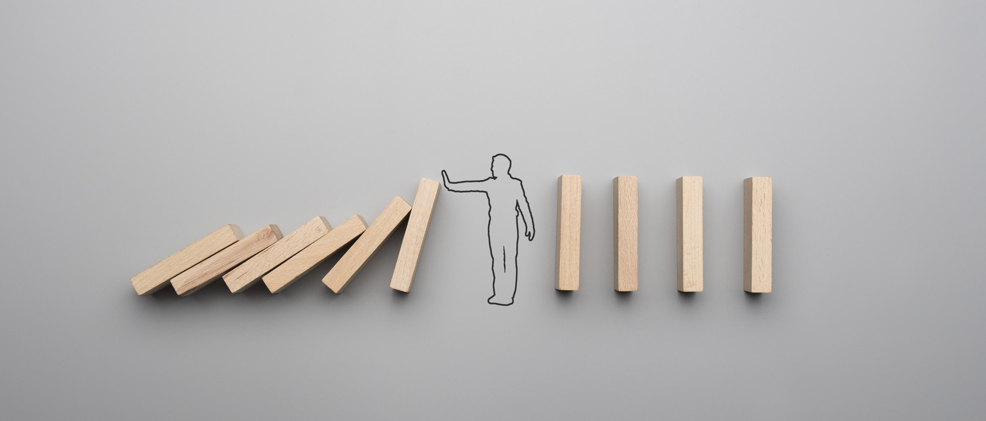 Mediator image - man stopping one party of blocks hitting the others