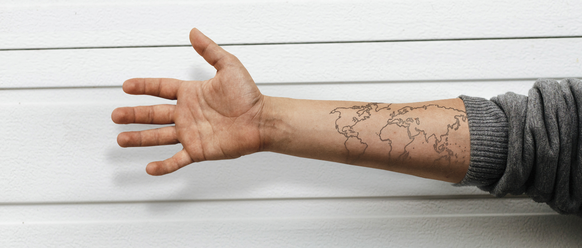 From a Western Missionary to African Pastors - image of a white man's arm reaching out with a world map tattoo