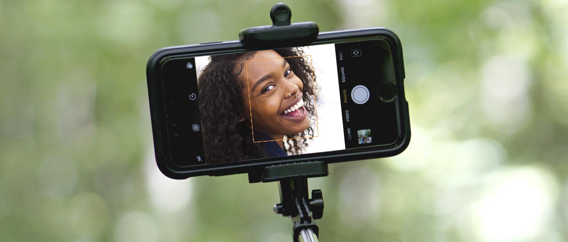Selfie image - African woman on phone screen