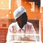 African woman seated inside behind a window with reflections all around her - what is my purpose she asks?