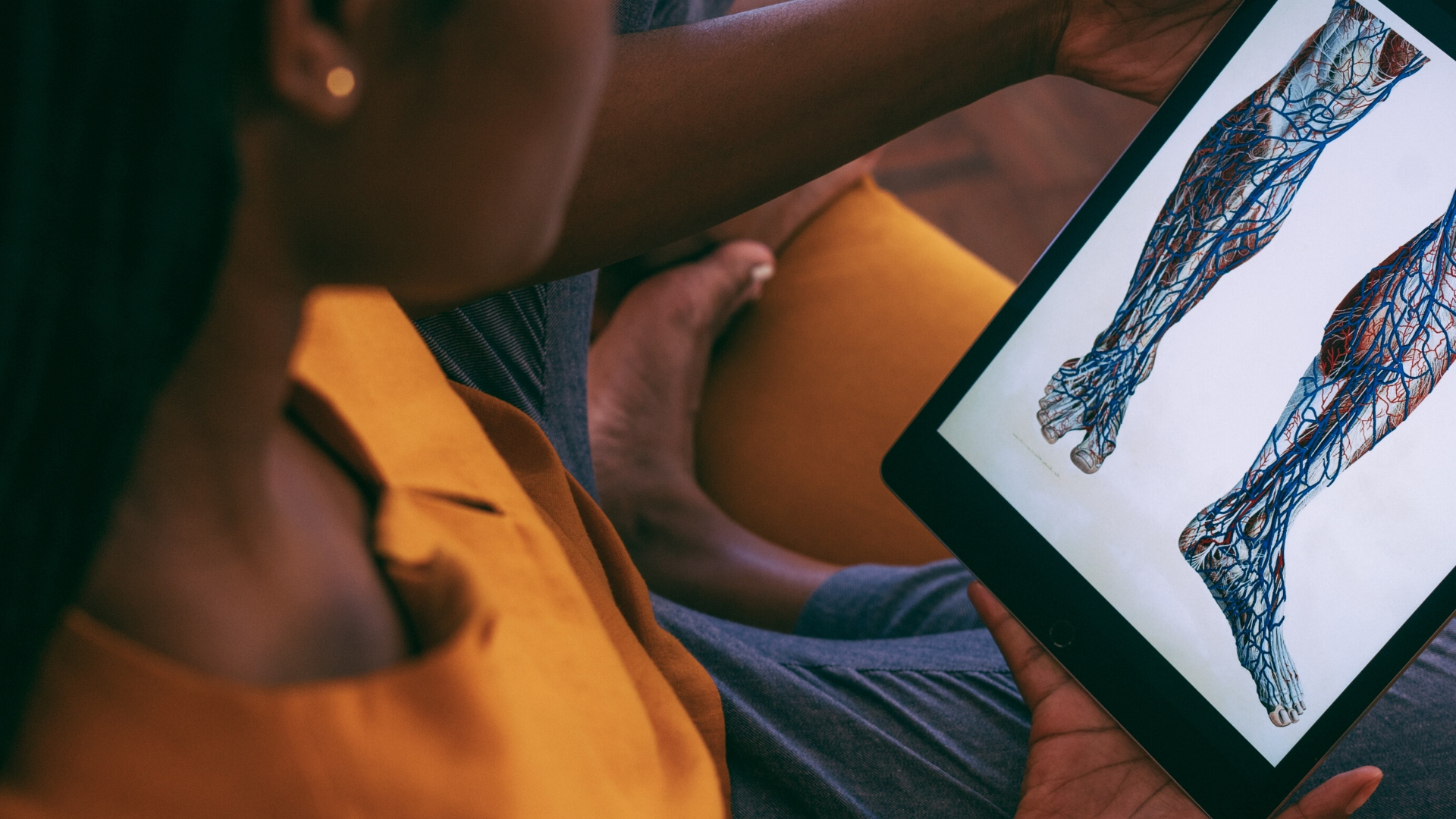 African woman on sofa looking at veins in leg on iPad