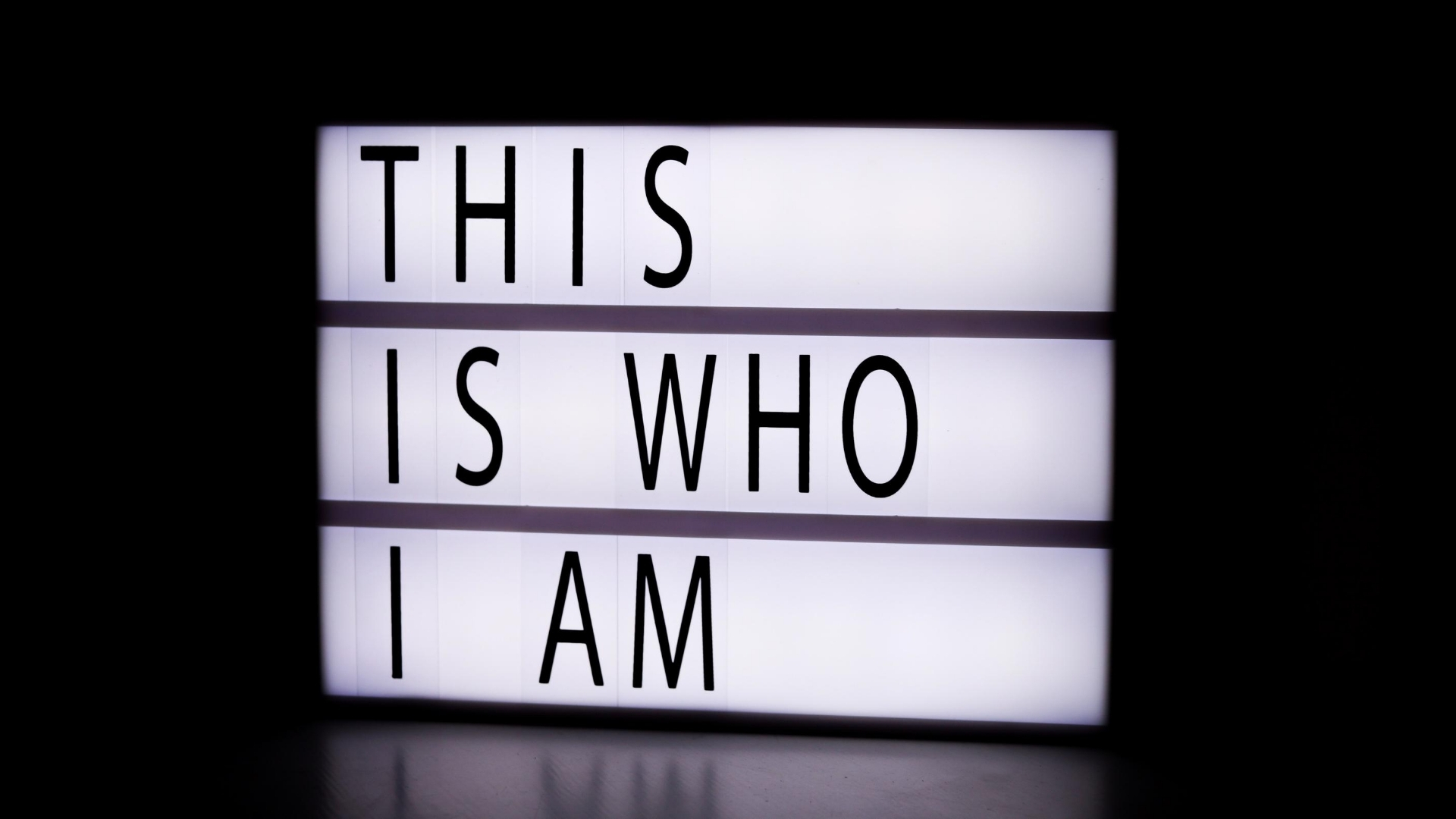 White Light-box in dark room with message in black: This is Who I AM