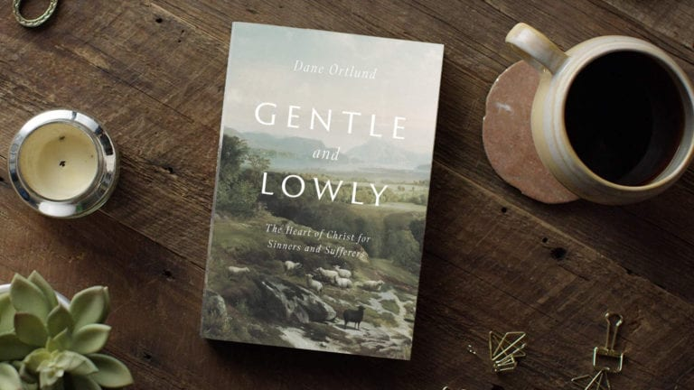 Gentle and Lowly book on a wooden table top with coffee and candle