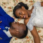 Couple from Rwanda lying on Bed in wedding clothes looking into each other's eyes - A you really ready for Marriage?