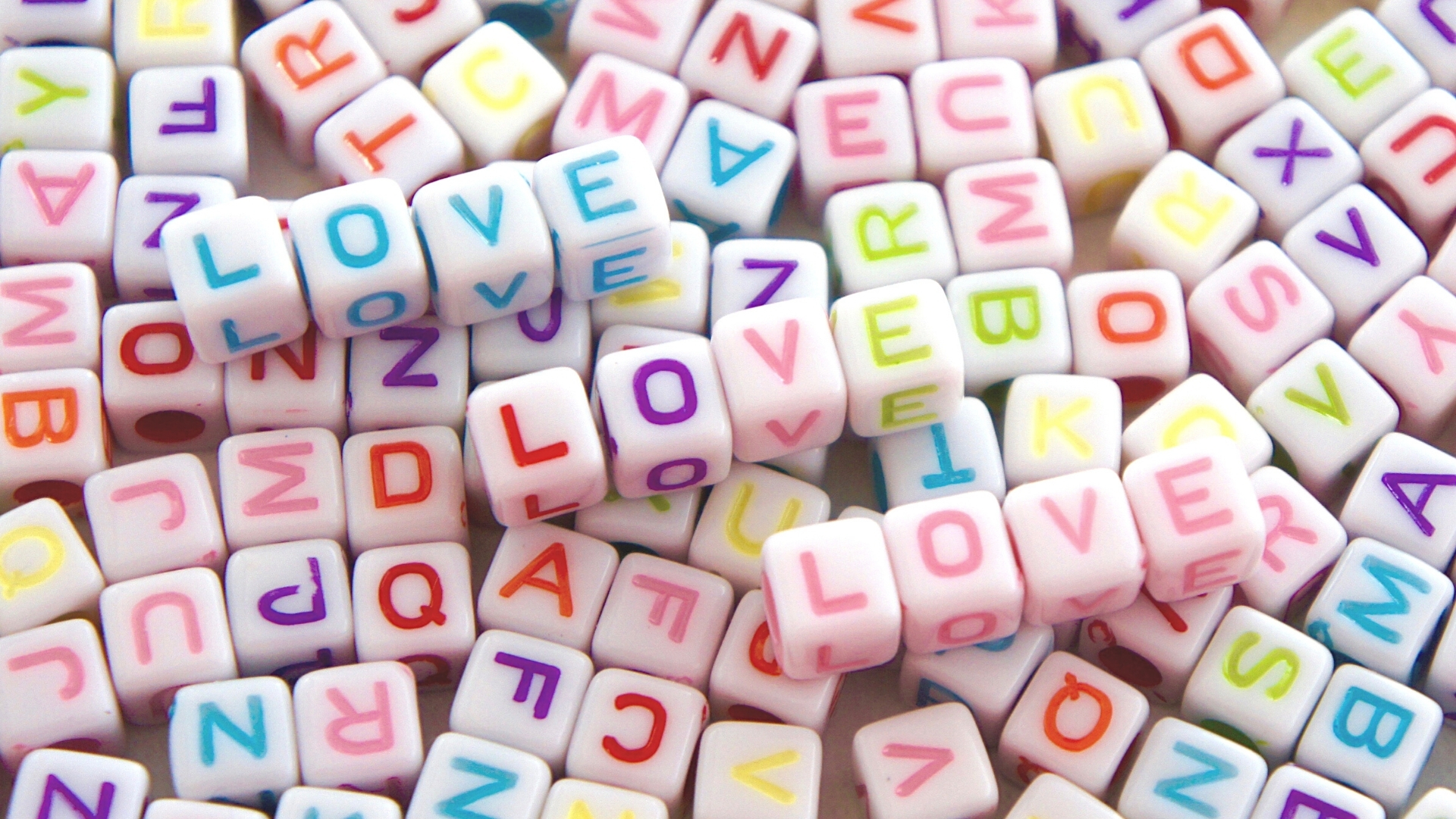 Love in letters of different colours - on top of a pile of other letter cubes
