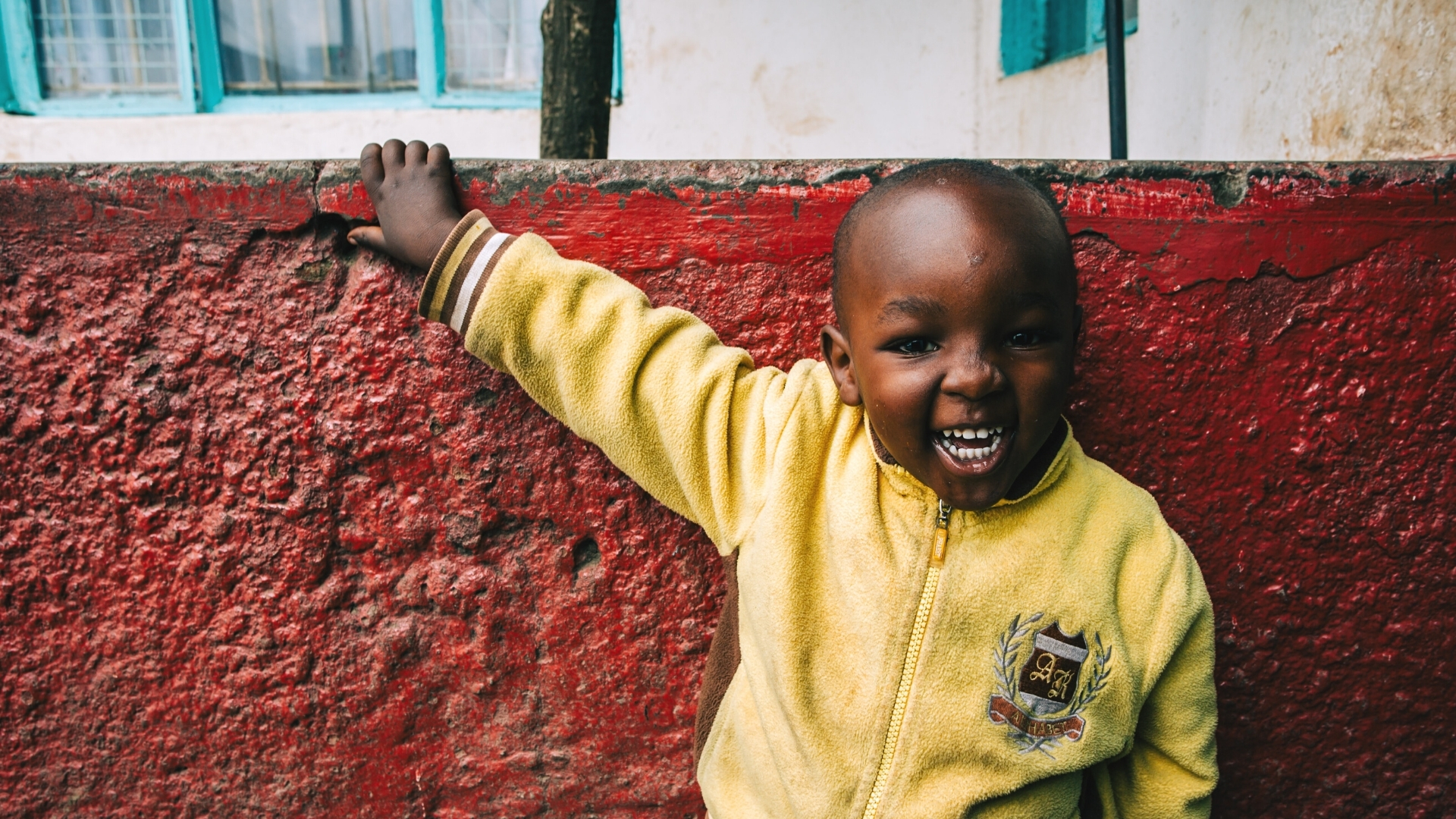 Love my non-christian neighbour - a little boy in Africa wearing a yellow top leaning against a red wall