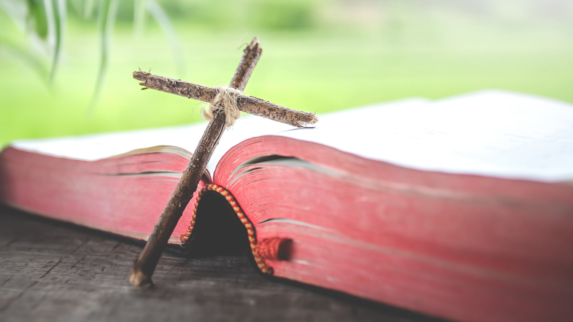 What is the Gospel? A cross of sticks with a big red Bible lying open on a table outside.