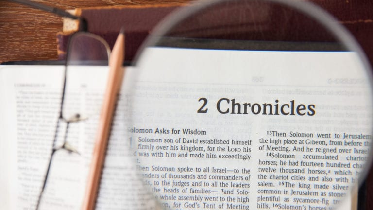 Does 2 Chronicles 7:14 explain COVID-19? Magnifying glass over 2 Chronicles page in Bible