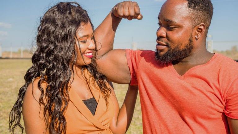 Zambian Couple - Man flexing his bicep as woman hugs him. Are Faithful husbands weak?