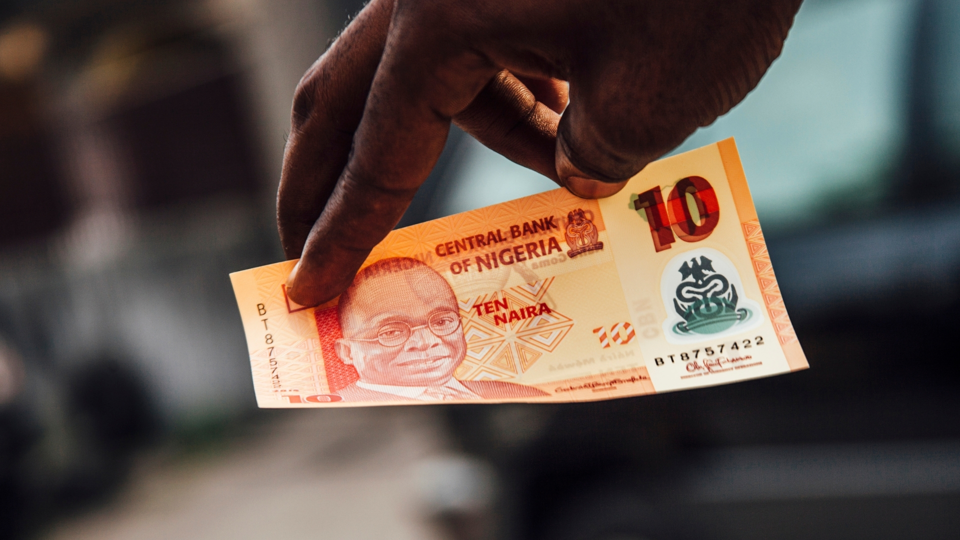 Should I tithe? 10 Naira note in someone's hand