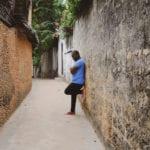Confess your sins - it's critical - African man leaning against ancient wall alone