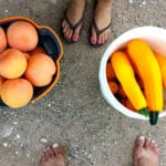 Christian growth makes you truly fruitful: African feet either side of two bowls of fruit and veg
