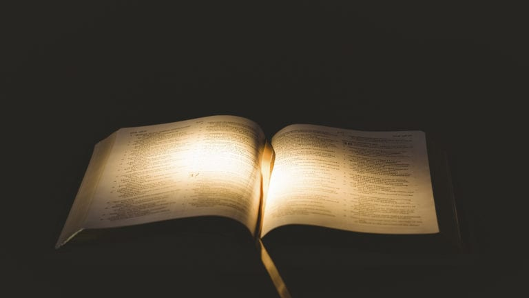 Expectations of the Bible: Open Bible in dark room with pages glowing bright
