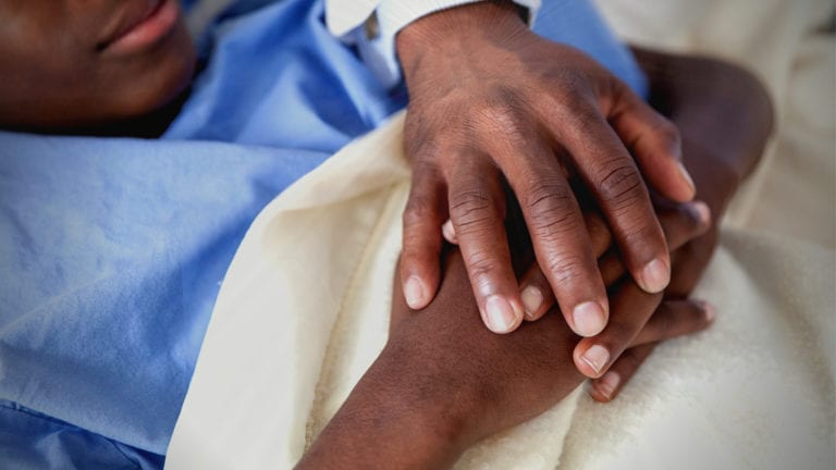 Do I need Angels to receive blessings? African man in hospital with a powerful hand over him, blessing him