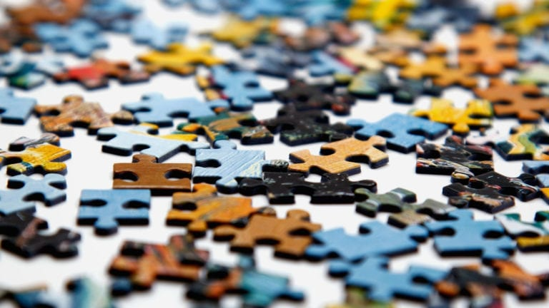 Making sense of Romans 8:28 means looking at the puzzle pieces together. Image of jumbled puzzle pieces on a white board.