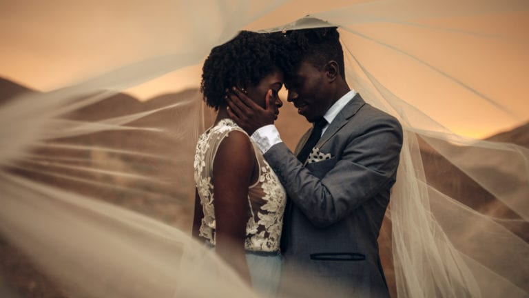 Healthy sex - an African married couple together inside a veil embracing