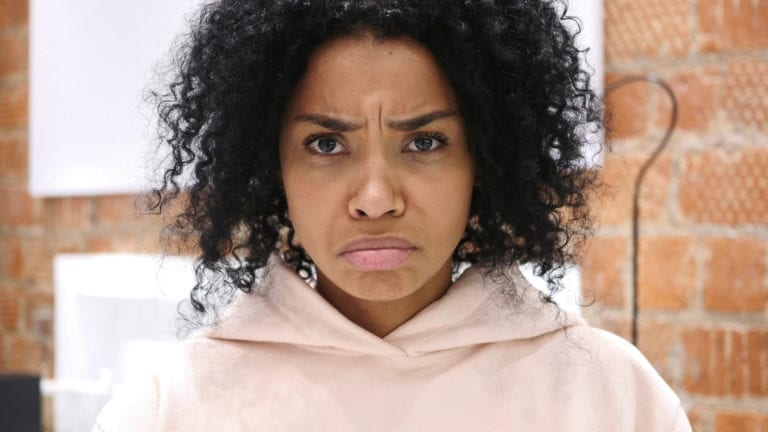 Dealing with church hurt: African woman looking very upset in pink top