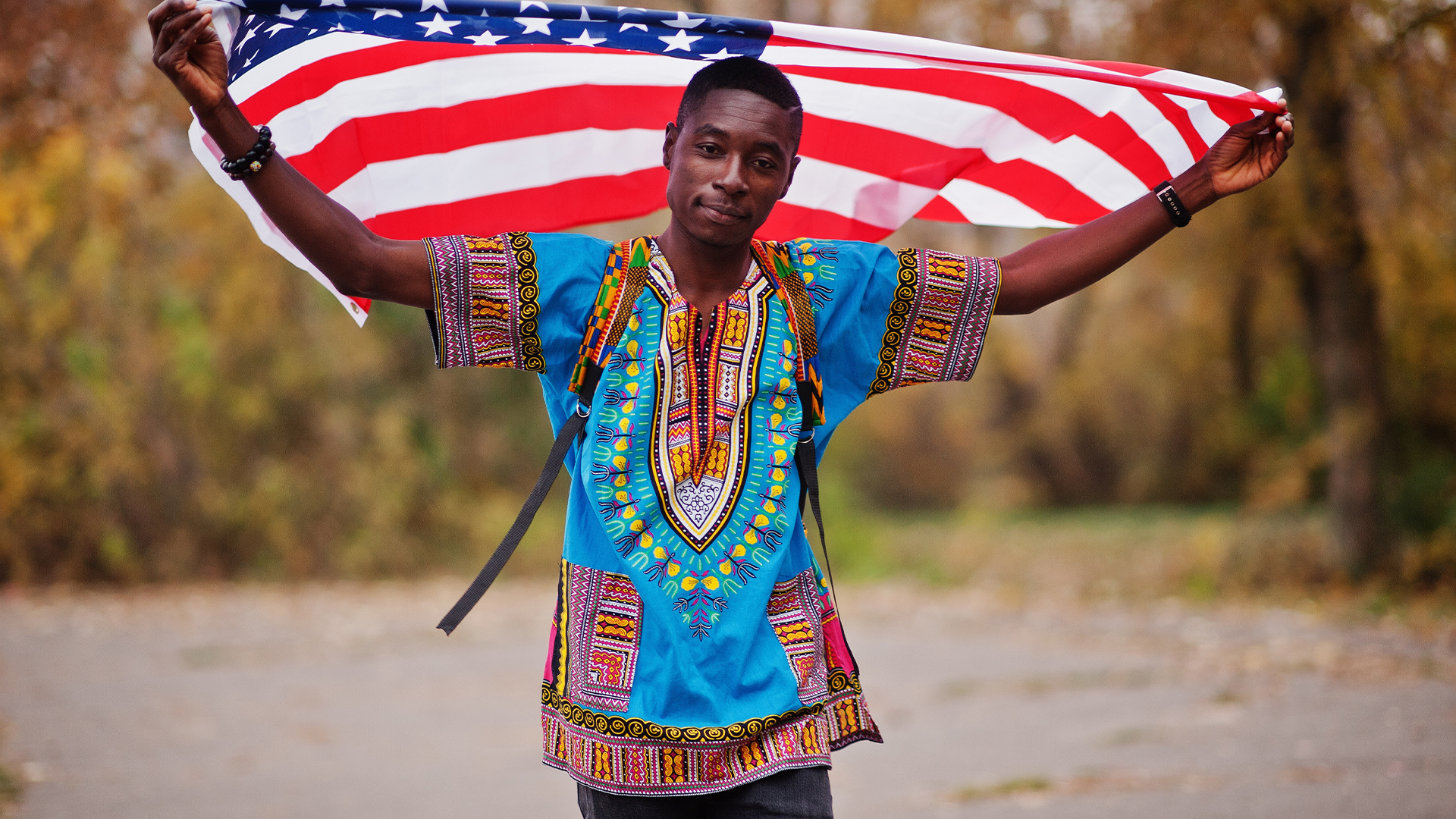 A picture of Heaven? African man holding the US flag over his head looking chuffed