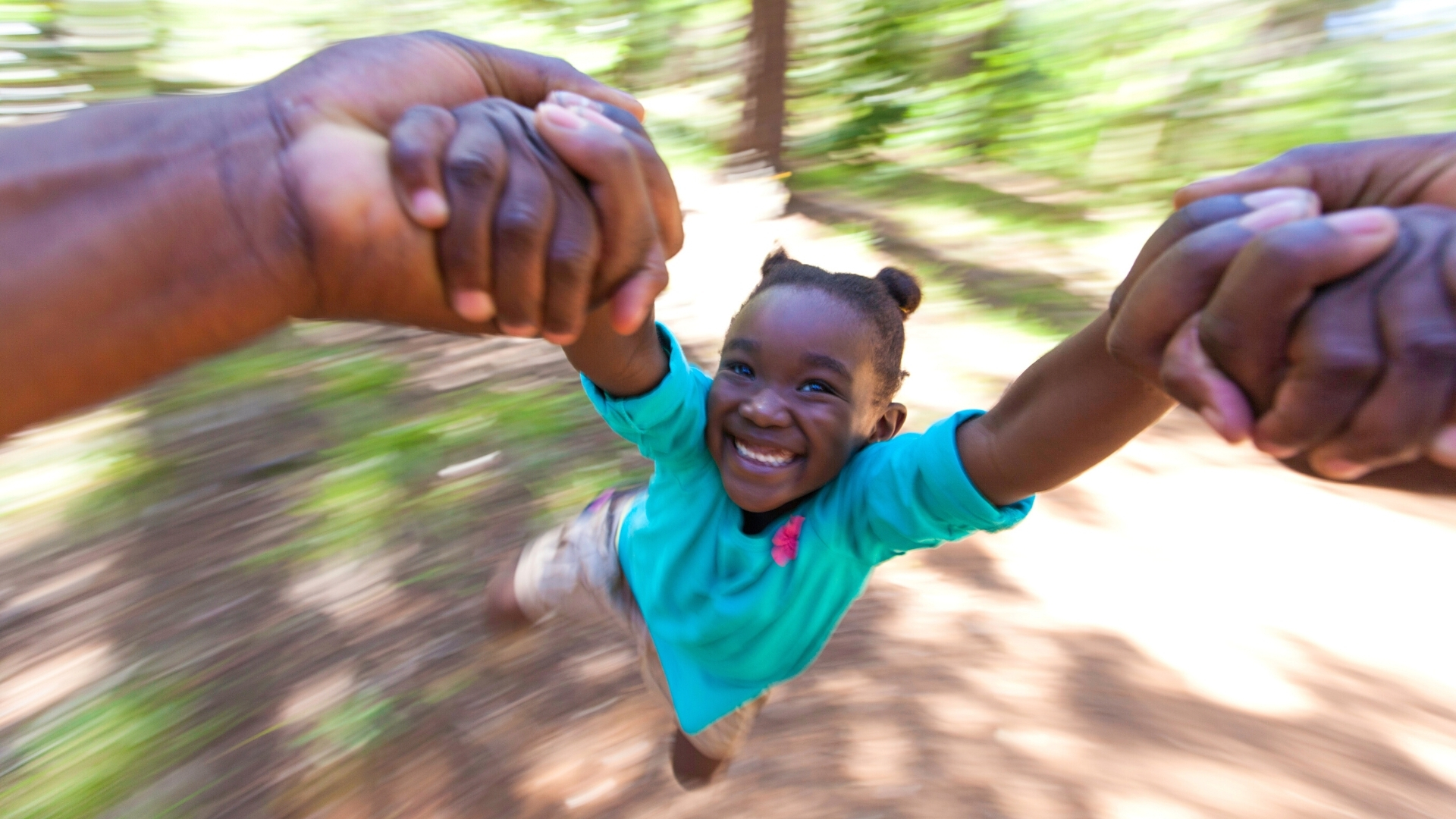 The joy of authentic humility - little African girl being made to fly by her loving father's hands