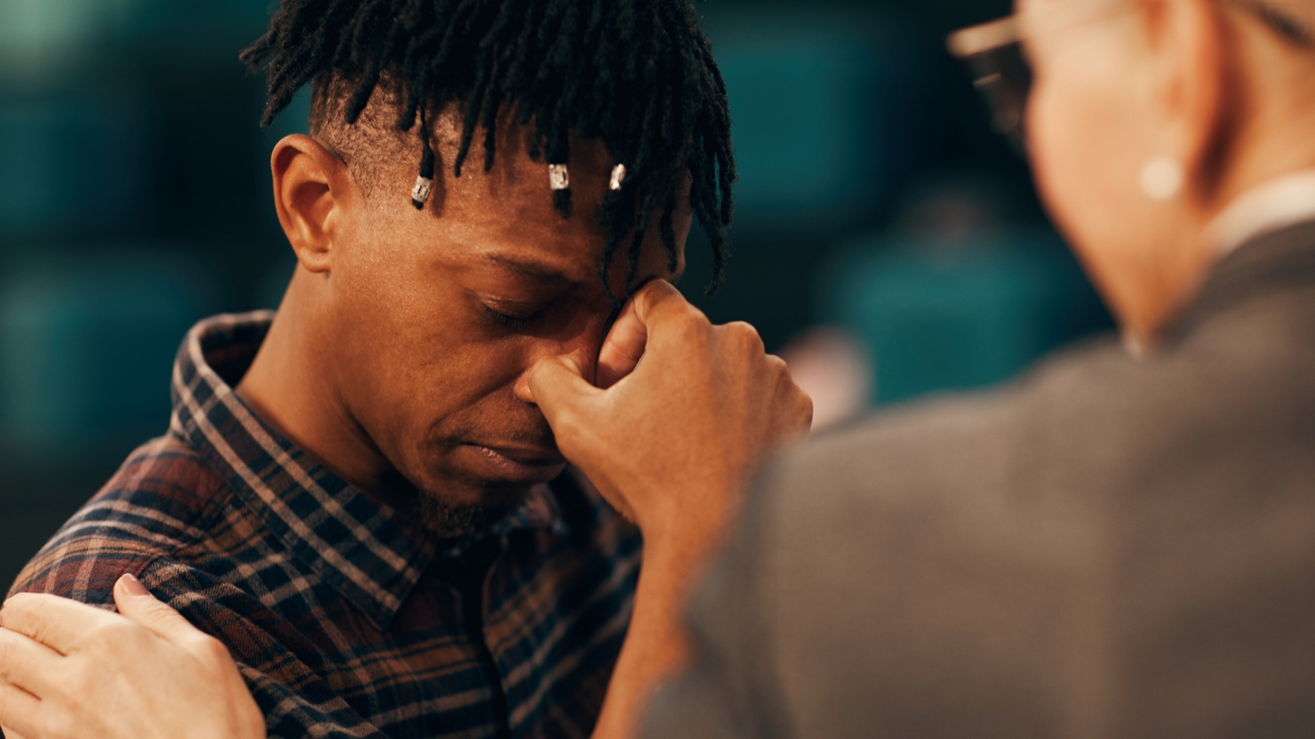 Can Christians mourn? Young African man weeping and being comforted
