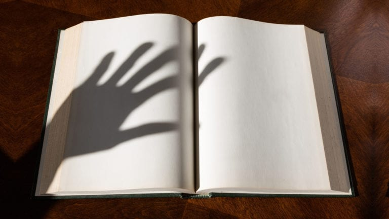 When deliverance goes wrong - unbiblical exorcism - a hand shadow over a blank bible