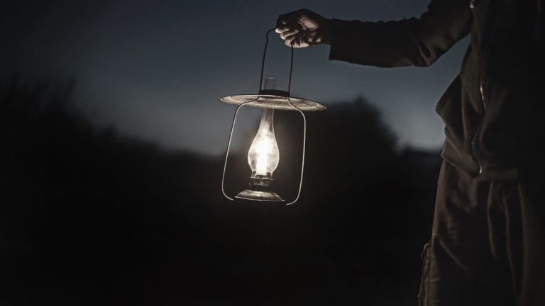 Spiritual Powers, witchcraft and christianity in Africa - a man holding a lantern in the darkness