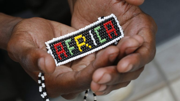 African culture & doing Church - Beaded Africa held in hands of African person