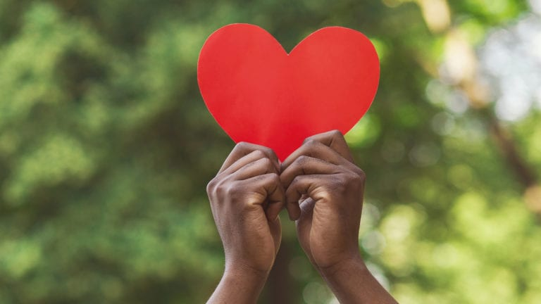 Should I Tithe or is it more about being generous? African hands holding up a red paper heart.