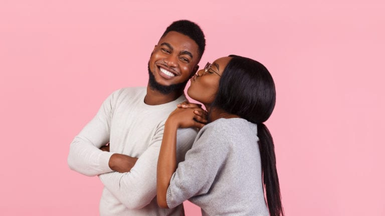To far? Physical affection while dating - African couple almost kissing on a pink background