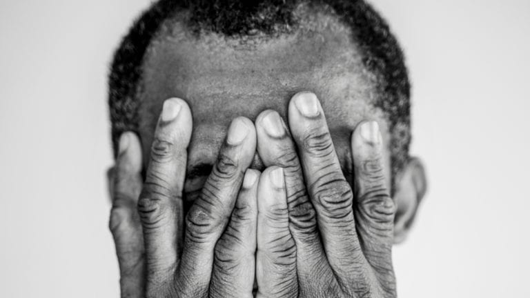 Amidst evil, violence and trauma, how do we pray? African man with his hands pressed over his face