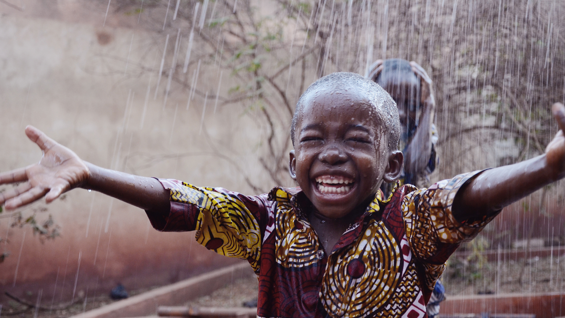 Africa is blessed not cursed! Small African boy grinning in the rain