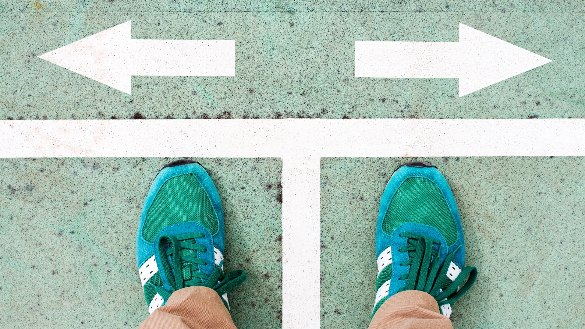 Which Career path? Person looking down on their green sneakers with arrows painted on the floor